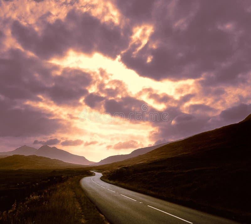 Strada con il tramonto delle montagne   fotografie stock