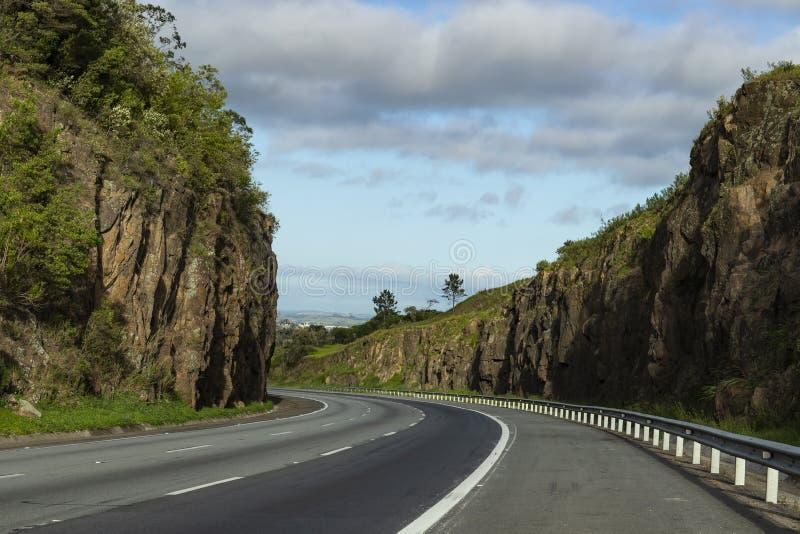 Strada con le pareti di pietra un giorno soleggiato Strada principale Presidente Castelo Branco, stato di sao Paulo Brazil immagini stock