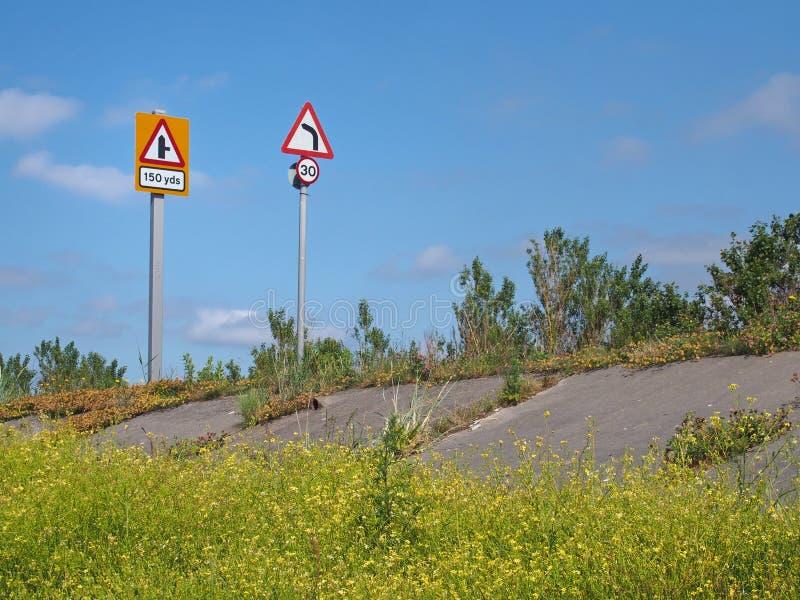 Strada costiera alzata lungo l'estuario ribble vicino a southport Merseyside con i segnali stradali limite di velocità e di giro immagini stock