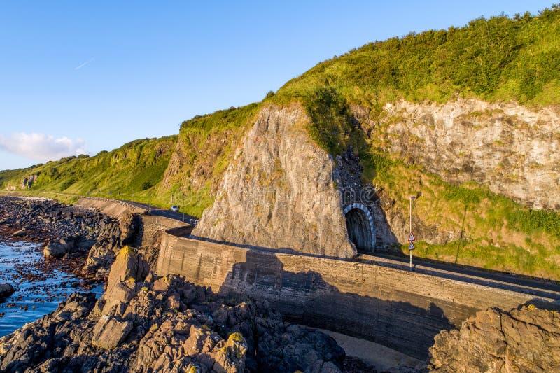 Strada costiera con il tunnel, Irlanda del Nord, Regno Unito fotografia stock libera da diritti