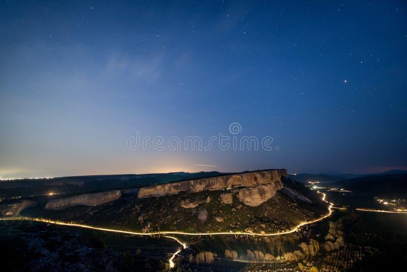 Strada d'ardore di notte nelle montagne sotto un cielo stellato fotografie stock