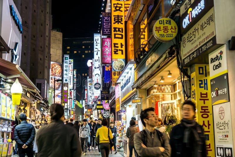 Strada dei negozi occupata di Myeongdong alla notte fotografia stock