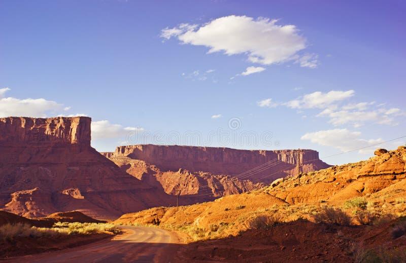 Strada del deserto attraverso Rocky Mesas al tramonto fotografia stock libera da diritti