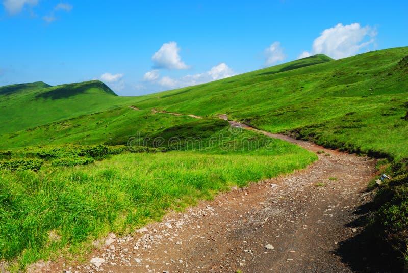 Strada della montagna alle colline verdi a distanza fotografie stock