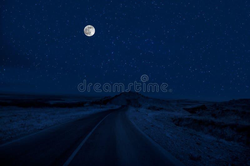 Strada della montagna attraverso la foresta su una notte della luna piena Paesaggio scenico di notte del cielo blu scuro con la l fotografie stock