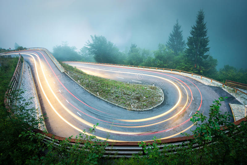 Strada della montagna di bobina con le luci dell'automobile Tempo piovoso e scarsa visibilità nebbiosi Alpi, Slovenia fotografia stock