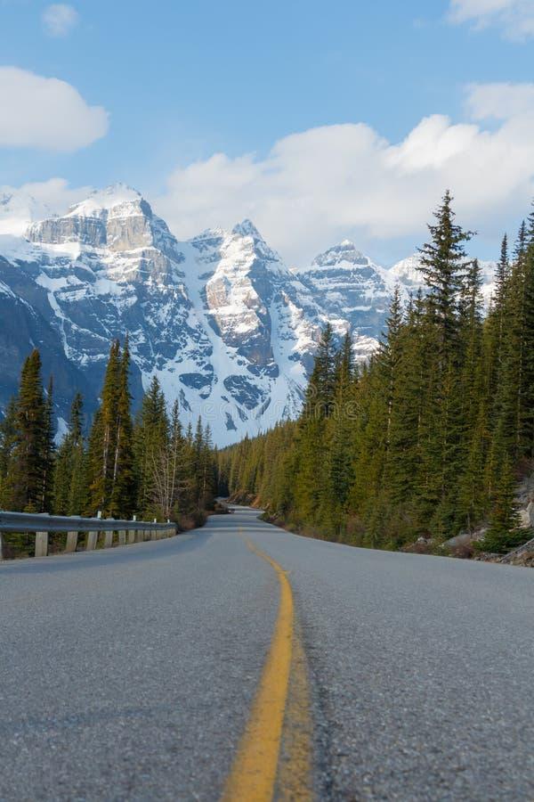 Strada di bobina che conduce alle montagne innevate fotografie stock libere da diritti