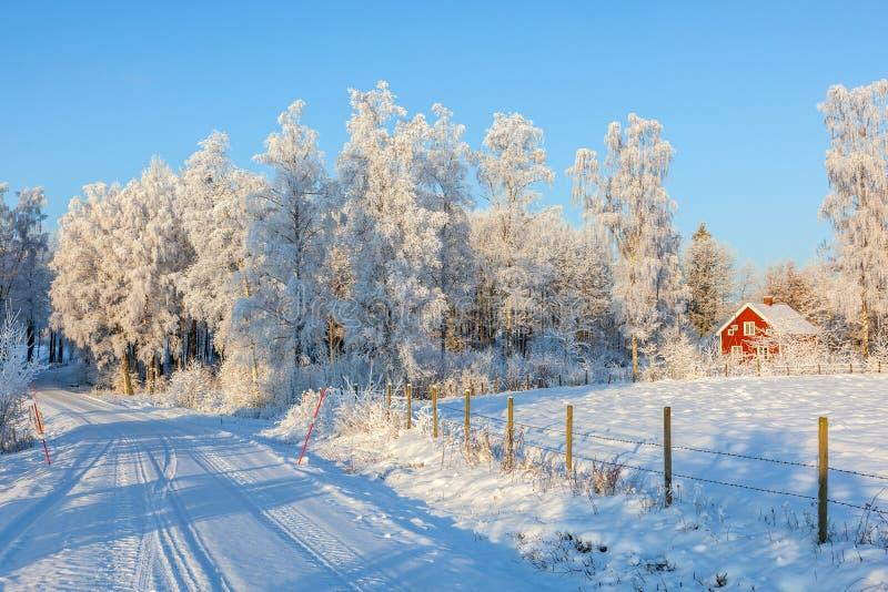 Strada di inverno con un cottage rosso fotografia stock