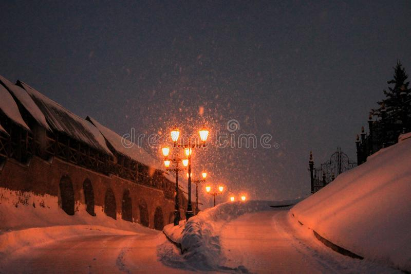 Strada di inverno e pali della luce, paesaggio di notte immagine stock