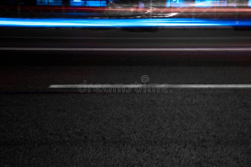 Strada di notte con le luci blu dalle automobili fotografie stock libere da diritti
