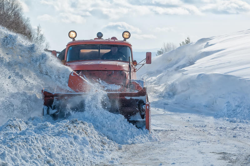 Strada di pulizia del camion nell'inverno fotografia stock
