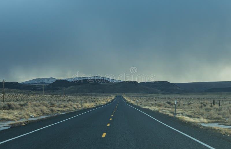 Strada diritta con le nuvole di tempesta avanti fotografia stock libera da diritti