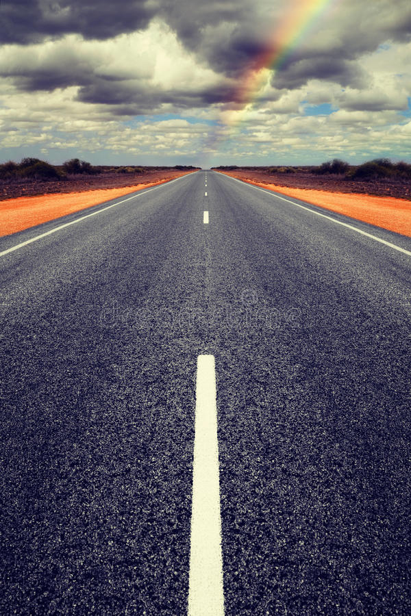 Strada diritta lunga con le nuvole di tempesta della riunione fotografia stock