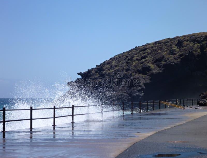 Strada e roccia alla spiaggia con lo spruzzo d'acqua fotografia stock libera da diritti
