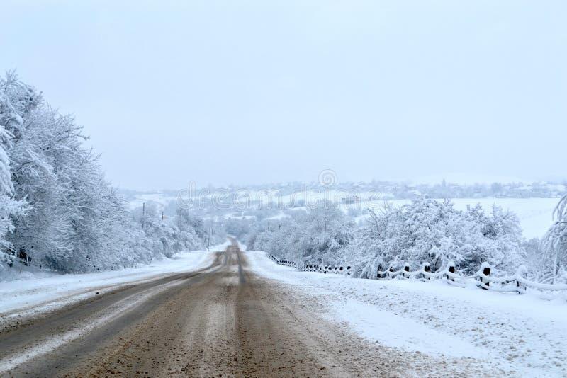 Strada ed alberi di inverno coperti di neve dopo le precipitazioni nevose Tempo del pericolo per guidare Asfalto ghiacciato roman fotografie stock