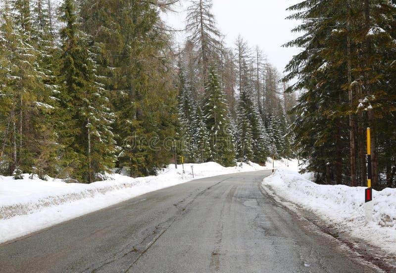 Strada ghiacciata della montagna con neve ai bordi fotografie stock