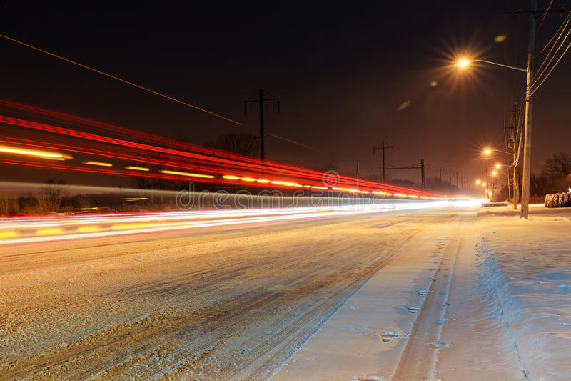 Strada innevata di inverno con i lampioni brillanti nelle zone rurali al tramonto fotografie stock