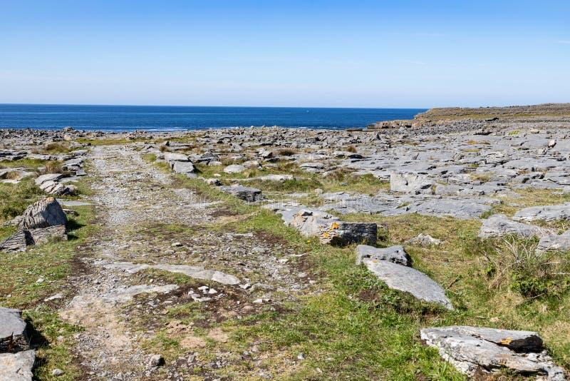 Strada intorno alle rocce con l'oceano nel fondo in Inishmore immagine stock libera da diritti