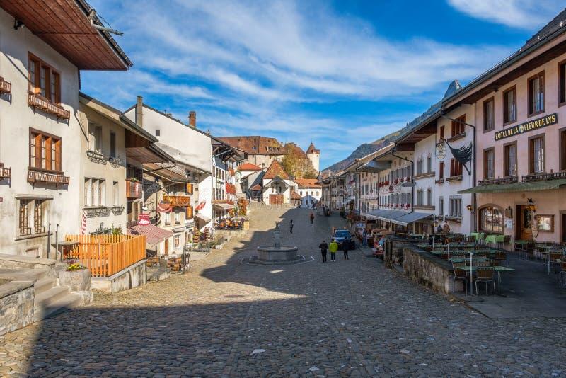 Strada medievale con i reatuarants fino al castello di Gruyeres, Svizzera, alla luce di autunno fotografie stock libere da diritti