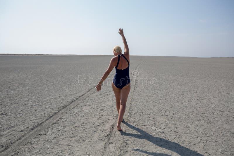 Strada nel deserto, donna di camminata immagine stock libera da diritti