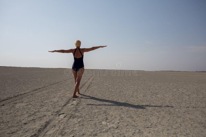 Strada nel deserto, donna di camminata fotografia stock