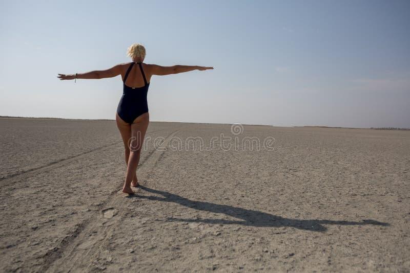 Strada nel deserto, donna di camminata fotografie stock