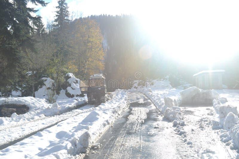 Strada nelle montagne, neve, sole, trattore fotografia stock