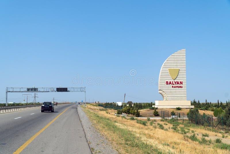 Strada nelle regioni di Azerbaigian, nome della città sull'insegna - rayonu di Salyan immagini stock