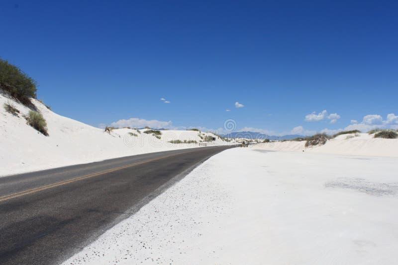 Strada nera, sabbia bianca brillante, & cielo blu profondo fotografie stock