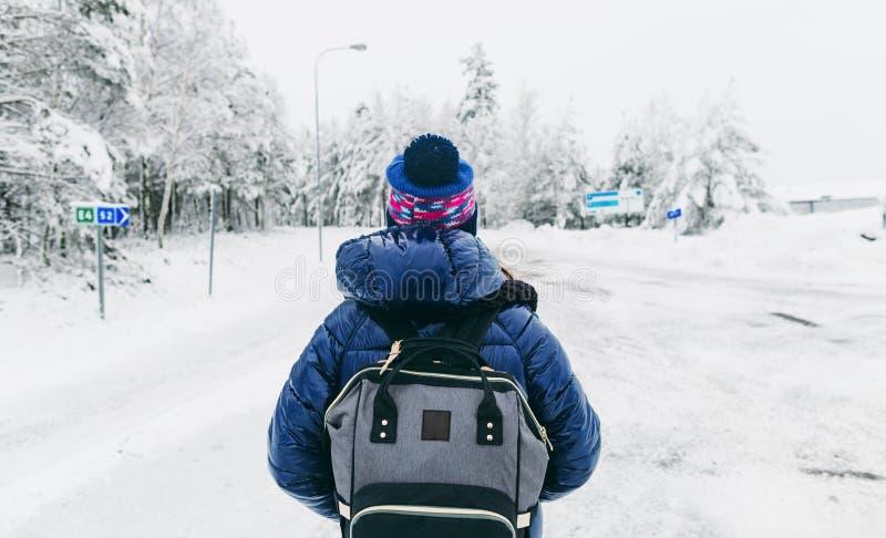 Strada nevosa di inverno dello zaino della giovane donna della Svezia di stile di vita di viaggio fotografia stock libera da diritti