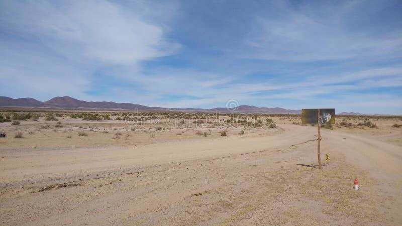 Strada non asfaltata ad elevata altitudine con il deserto sabbioso al sale di Uyuni in BO immagine stock libera da diritti