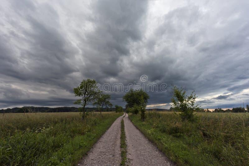 Strada non asfaltata ed il cielo nuvoloso scuro immagine stock