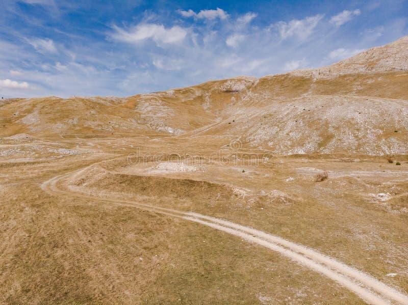 Strada non asfaltata in steppa a distanza della Bosnia immagini stock libere da diritti