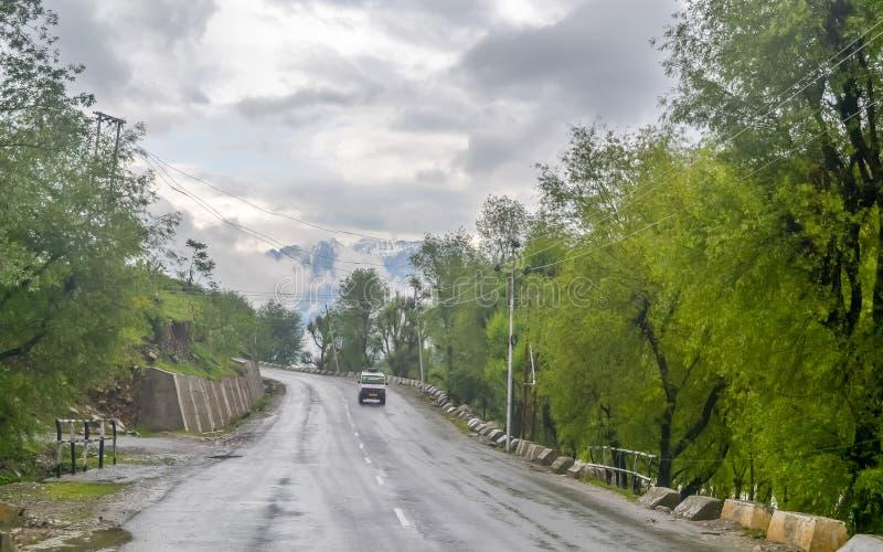 Strada perfetta della montagna dell'asfalto nel giorno piovoso nuvoloso Percorso in salita che conduce da parte a parte Carreggia fotografie stock