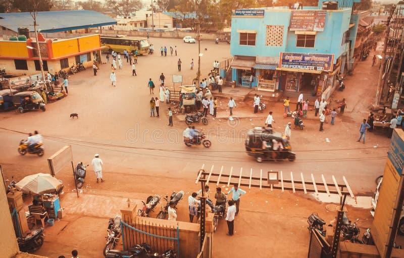 Strada in piccola città indiana con le bici, il taxi e la gente di camminata fuori immagine stock