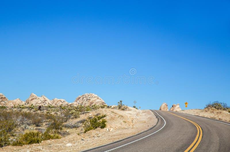 Strada principale attraverso un paesaggio del deserto con le montagne ed il fogliame verde immagine stock