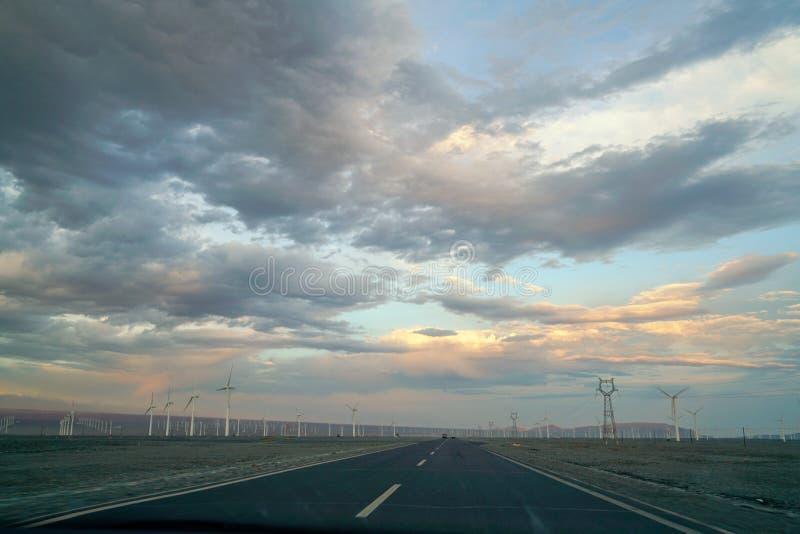 Strada principale con i generatori eolici al tramonto con le belle nuvole fotografia stock libera da diritti