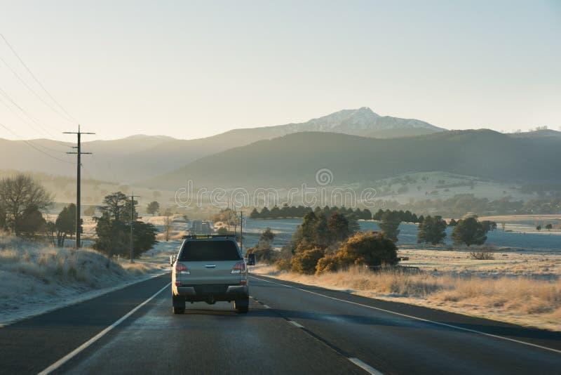 Strada principale del paese con le automobili che conducono verso le montagne all'alba fotografia stock libera da diritti