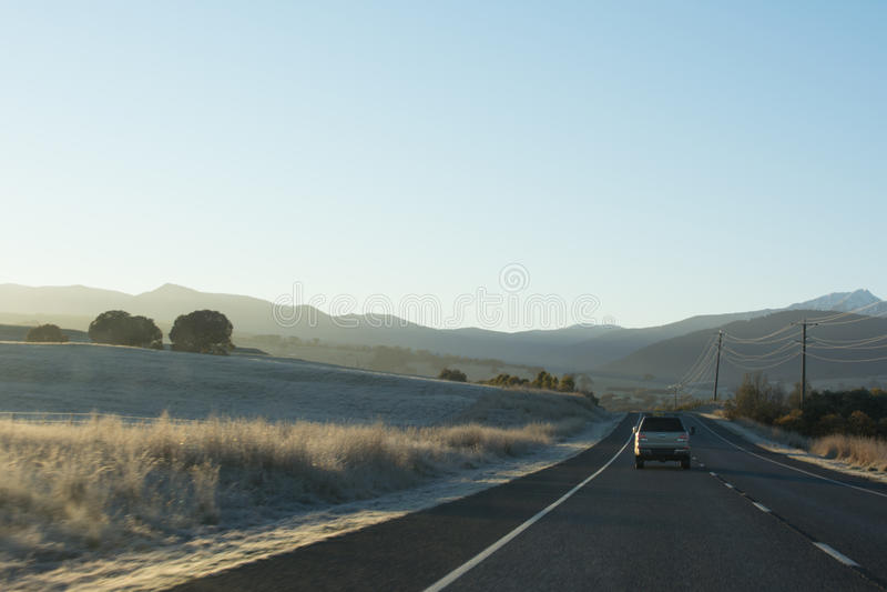 Strada principale del paese con le automobili che conducono verso le montagne all'alba fotografia stock