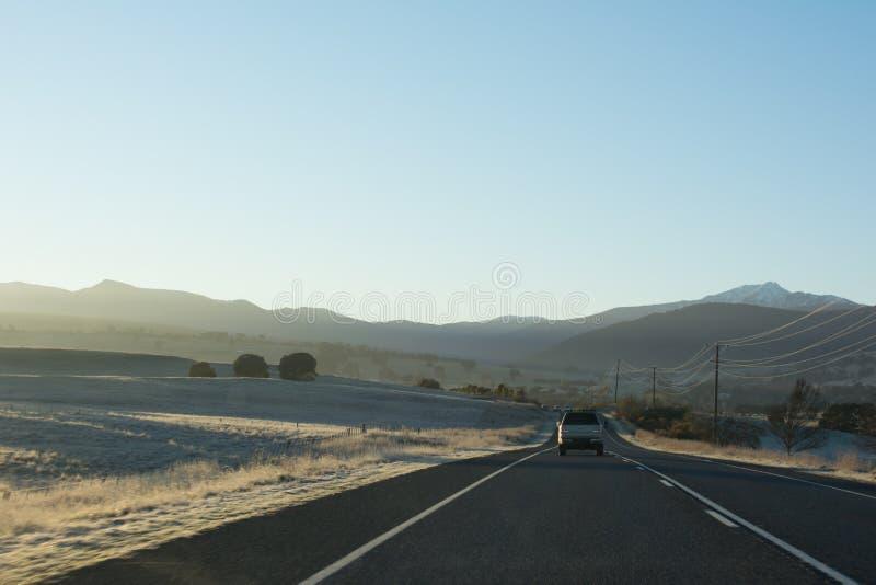Strada principale del paese con le automobili che conducono verso le montagne all'alba immagine stock