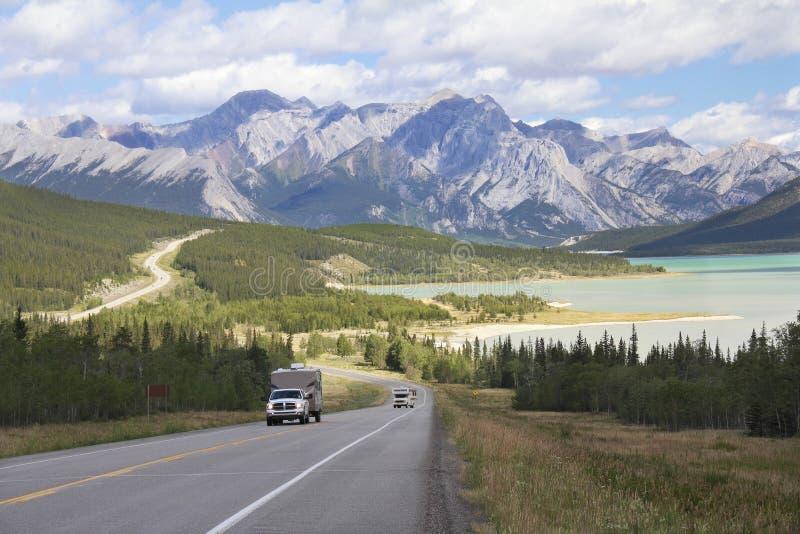 Strada principale di bobina accanto ad un lago mountain - Alberta, Canada fotografia stock