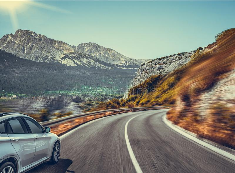 Strada principale fra il paesaggio della montagna Automobile bianca su una strada della montagna immagini stock libere da diritti