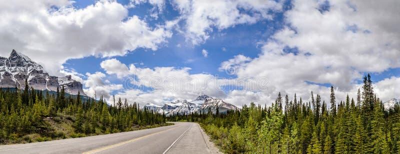 Strada, strada principale fra le montagne della neve e la foresta verde immagine stock
