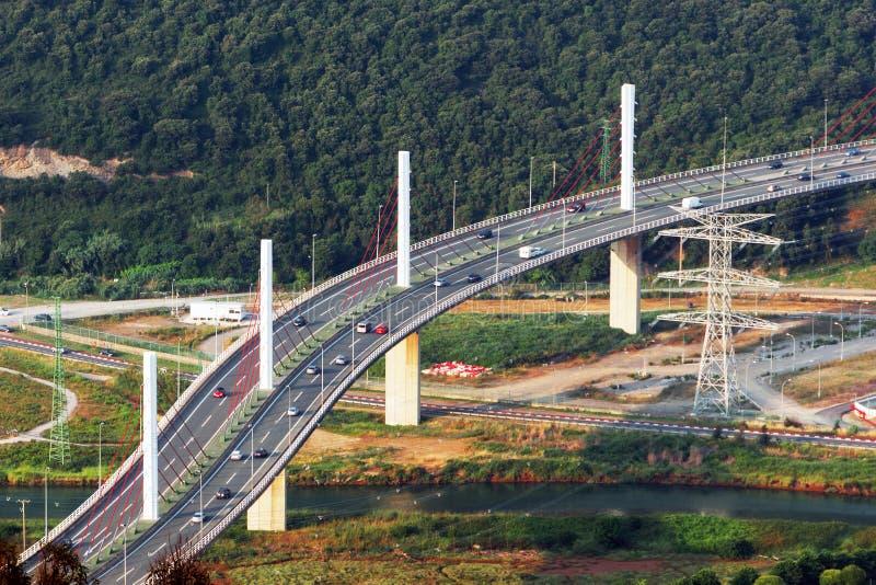 Strada principale sulle automobili e sulle colonne del briciolo del ponte immagine stock libera da diritti