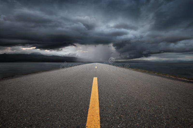 Strada principale vuota che conduce alle montagne attraverso la pioggia fotografia stock libera da diritti