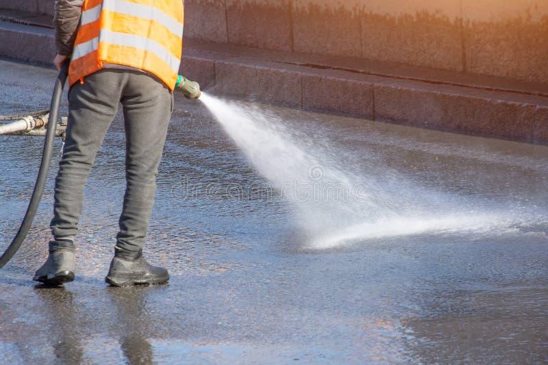 Strada privata di pulizia del lavoratore con la rondella ad alta pressione della benzina che spruzza la sporcizia, strada asfalta immagine stock libera da diritti