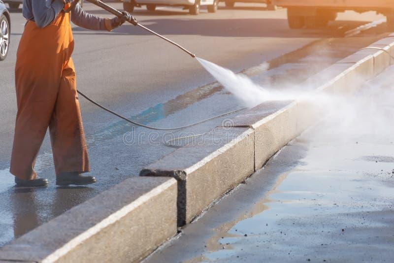 Strada privata di pulizia del lavoratore con la rondella ad alta pressione della benzina che spruzza la sporcizia, confine della  fotografia stock