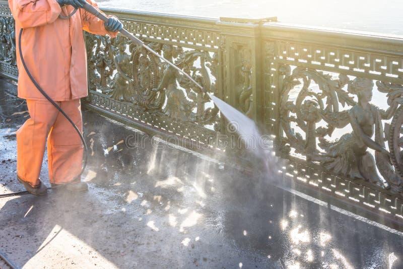 Strada privata di pulizia del lavoratore con la rondella ad alta pressione della benzina che spruzza la sporcizia, inferriate, po fotografia stock libera da diritti