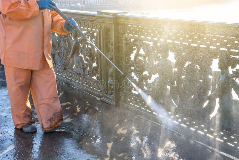 Strada privata di pulizia del lavoratore con la rondella ad alta pressione della benzina che spruzza la sporcizia, inferriate, po fotografie stock