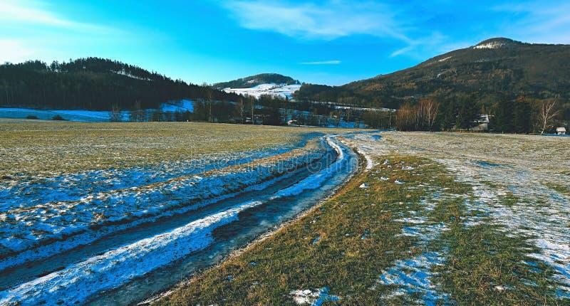 strada rurale attraverso un campo di neve di fusione in molla in anticipo fotografia stock